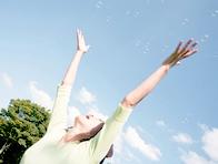空に向かって手を伸ばす女性